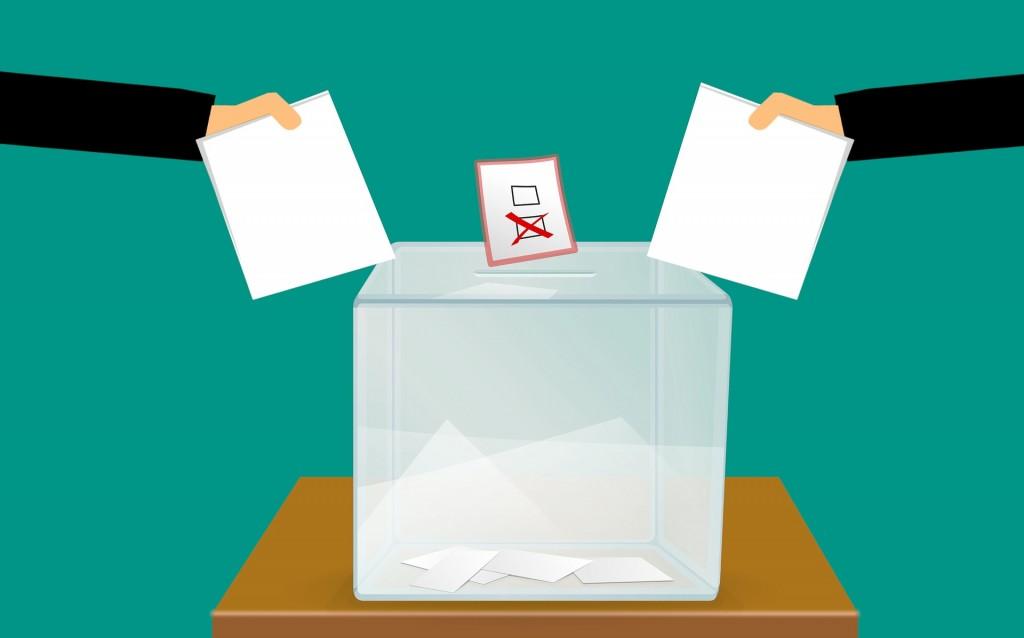 b0d1dddc96b9cf Obrazek ilustrujący urnę wyborczą, do której wrzucane są karty wyborcze.